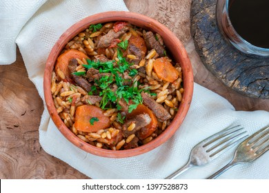 Giouvetsi - traditional Greek baked dish with beef and orzo pasta in tomato sauce - top view