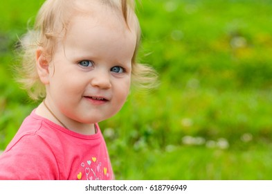 The girl is 1 year old, blonde, with blue eyes. Cute baby close-up on a green park background.