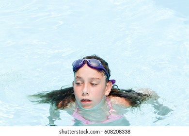 Girl 10 years old with gogles in swimming pool