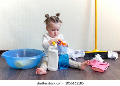 a girl of 1.5 years old sits on the floor and studies bottles with household chemicals, Dangers for children in the home