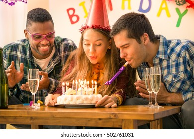 Girl 18th birthday party with happy multiracial friends  - Young woman blowing on cake candles in festive moment together - Concept of friendship joy and the coming of legal age - Focus on girl face