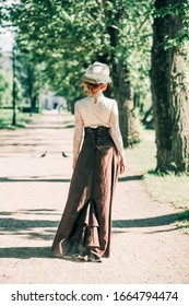 A girl in a 19th century dress walks in the Park