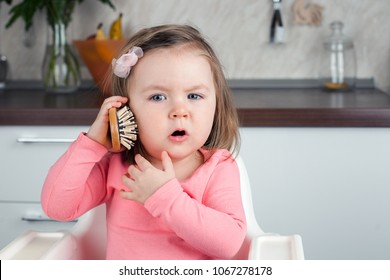 girl 2 years old playing with a comb at home - portraying an emotional conversation on the phone
