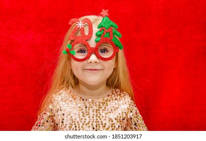 girl 4 years old blonde with long loose hair wearing new year's glasses with the numbers 2021 close up on a red background