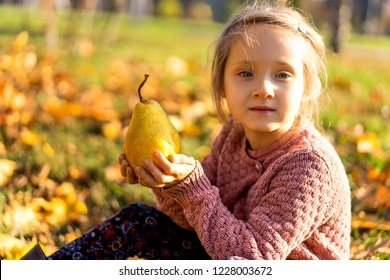 girl 4 years old walks in autumn park holding a pear