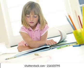 Girl (4-6) looking at book, low angle view (tilt)