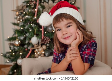 girl 5 years old in a red cap of European appearance sits near the Christmas tree