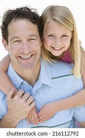 Girl (5-7) with arms around father, smiling, portrait