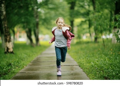 Girl 6-7 runs in the autumn park