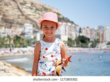 Girl 6-7 years old on Postiguet beach, looking at camera. Santa Barbara castle fortification, swimming and sunbathing people on background. Summer holidays concept. Alicante. Costa Blanca. Spain
