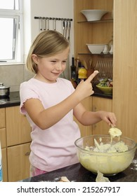 Girl (6-8) standing in kitchen, dipping finger into bowl of cake mix, holding spoon, smiling
