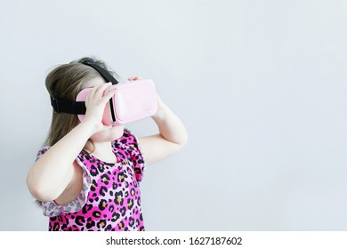 Girl 7-8 year old using the virtual reality headset. Copy space