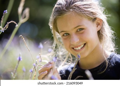 Girl (8-10) in field, smiling, portrait, close-up