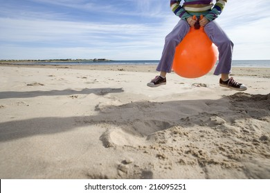 Girl (8-10) playing on inflatable hopper on beach, low section