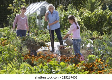 Girl (8-10) watering flowers in garden, mother and grandmother looking on, smiling, side view