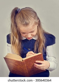 the girl of 9 years in a school uniform reads the book. The image is stylized by an abstract background.