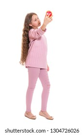 A girl of about eleven with long hair attentively examines herself in the mirror