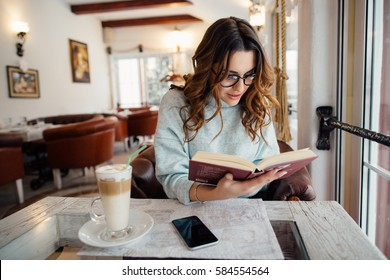 Girl absorbed in reading book during the break in cafe