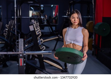 Girl adds weight to the bar. Asian woman adding weight on a bar as she workout in fitness gym