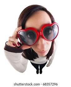 Girl adjusting her heart-shaped sunglasses and looking straight at camera. Shot using a fish eye lens from high angle.