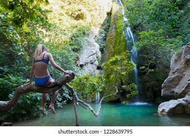 A girl admiring the Richtis Gorge waterfall. It is a state protected park near Exo Mouliana, Sitia, eastern Crete. The hiking trail is about 4 km in length of easy to moderate difficulty.