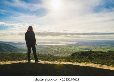 Girl admiring a scenic view from the top of a hill in Cap de Creus peninsula, north Catalonia, Spain