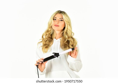 Girl adorable blonde hold curling iron white background. Form exquisite curls and romantic light waves. Heat setting for hair type. Woman with long curly hair use curling iron. Hairdresser equipment