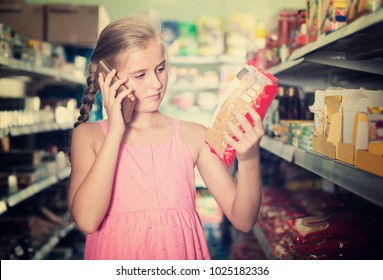 Girl is advised by phone what pasta she should buy in supermarket.