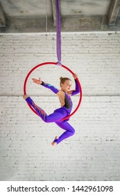 girl aerial gymnast on a circle doing acrobatic elements.