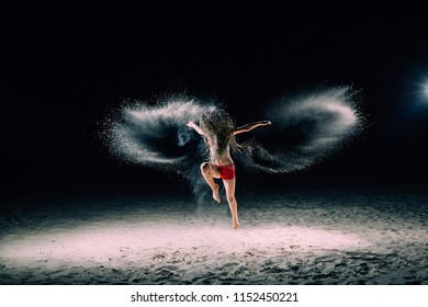 The girl with the African braids is jumping at night on sand. The face covered with hair. Sand is scattering everywhere. Backlight