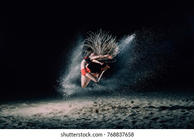 The girl with the African braids is jumping at night on sand. Sand is scattering everywhere. Backlight