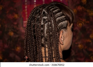 Girl with the African pigtails. View from the back