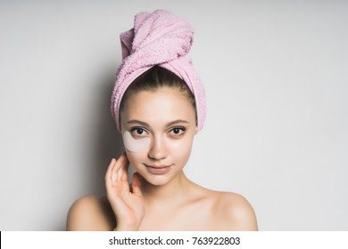 girl after shower with pink towel on her head cute looks at camera, isolated on white background