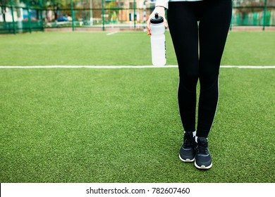 Girl after training, running or sports a rest. In the foreground, a bottle of water. The Girl works in the open, fresh air. Isolated place for text