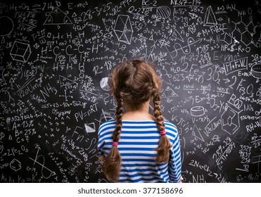 Girl  against big blackboard with formulas, back view