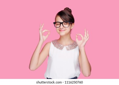 Girl against pink background showing ok gesture dreaming with closed eyes