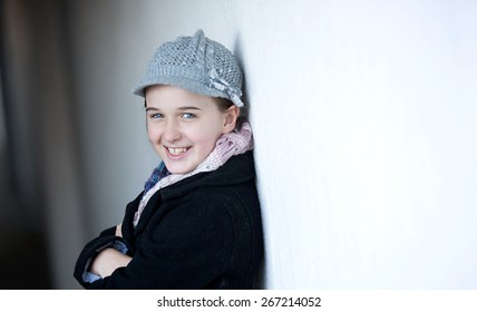 Girl against a white wall smiling with winter clothing on