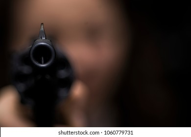 the girl is aiming from the revolver right into the photographer. focus on the muzzle of the revolver. the girl's face is blurry