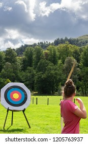 A Girl Aims her Bow and Arrow at an Archery Target in teh Scottish Countryside