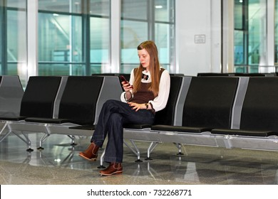 Girl at an airport making a call while waiting for her flight
