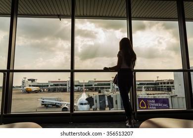 Girl at the airport window, Bangkok - August 6: Don Muang Airport on 3 November , 2015  at Don Muang Airport in Bangkok, Thailand.