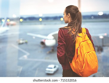 Girl at the airport window looking outside