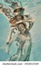 A girl in an airy light dress swims underwater as if flying in zero gravity