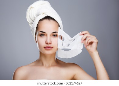 Girl with almost rended white mask. Model pulling away mask from her face. Hair wrapped with towel. Head and shoulders, studio, indoors