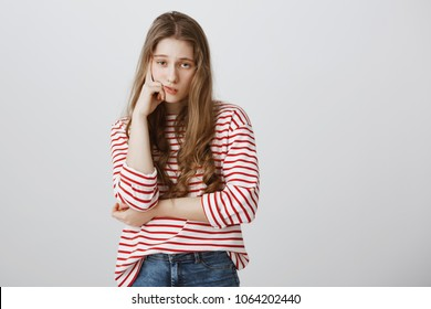 Girl almost sleeps from boredom during class. Portrait of indifferent tired female model supporting head with hand, slouching with drooping eyes, being interested in event, exhausted during date