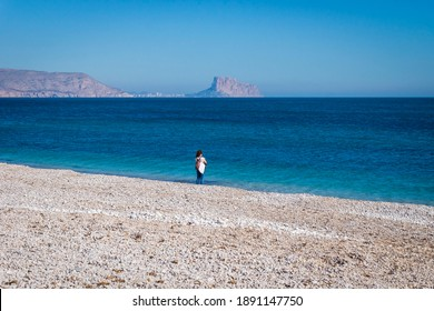 Girl alone on the stone beach of Albir with view over ocean to rock of Calpe, Albir, Costa Blanca, Spain