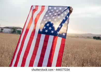 Girl with american flag smiling in the sunset. Young woman playing with USA flag in the 4th of July.