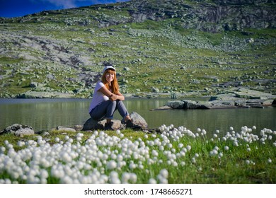 girl among a field of dandelions. Girl in a white hat in the summer with white dandelions, Norway.