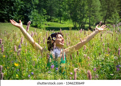 girl among spring flowers smiling and breathing pure air