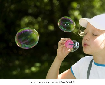 The girl amuse oneself, starting up multi-colored soap bubbles